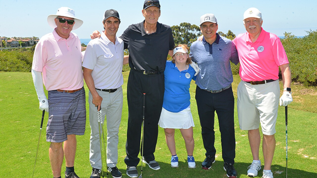 Amy standing side by side in a group with Rick Barry and celebrity golfers.