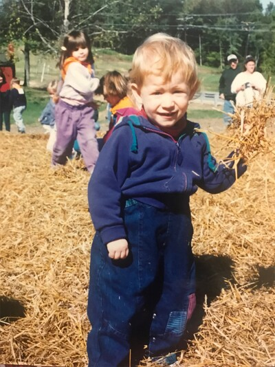 A photo of young RJ playing in a pumpkin patch.