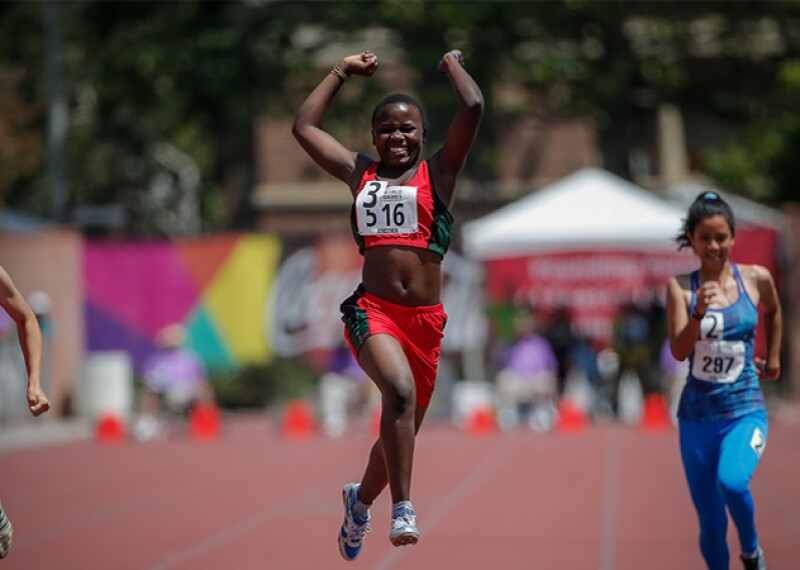 Young woman reacts as she crosses the finish line ahead of two other athletes in the ladies 100 meter final division 01.