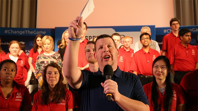 Man speaking into a microphone he's holding in his left hand and his right hand up holding note cards. Spectators are behind him.