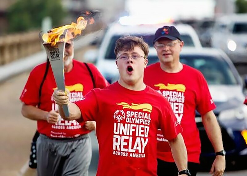 Athlete running in the street with the Eternal Flame of Hope.