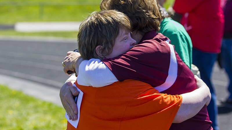 Athlete hugging his mother outside next to a track.