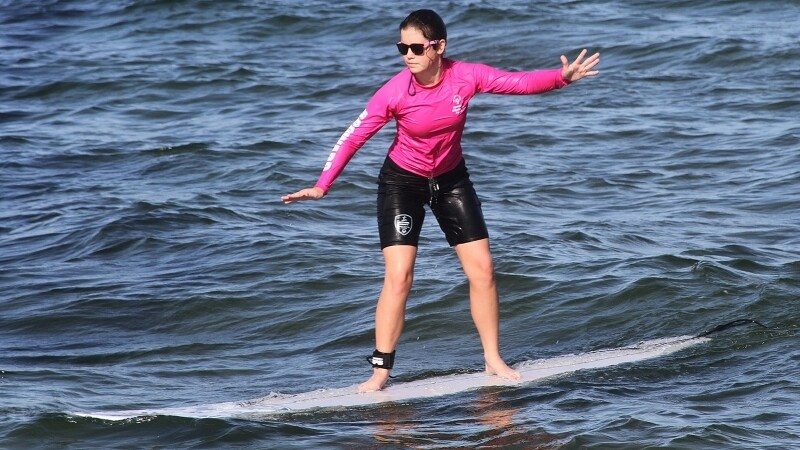 Special Olympics athlete surfs in the ocean.