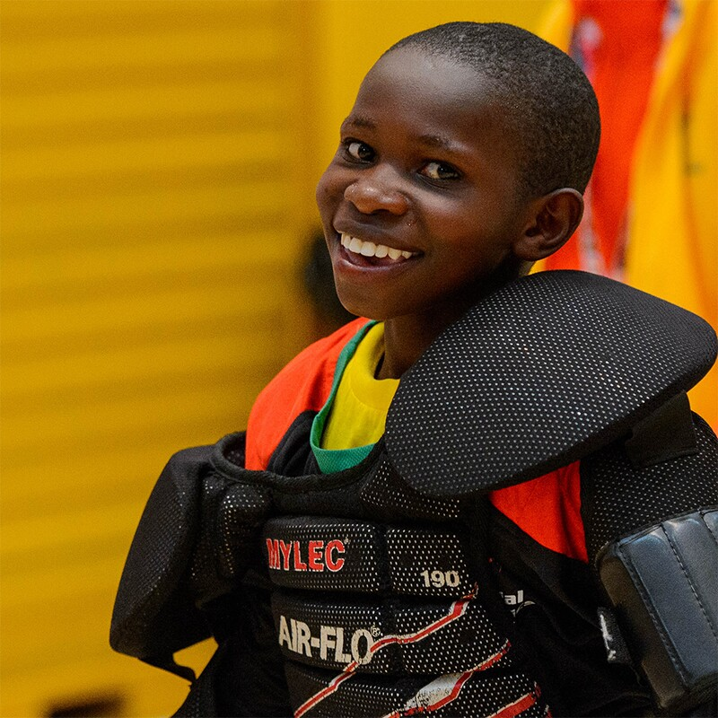 Lawrence Mwangi dressed in his goalies uniform and smiling for the photo.