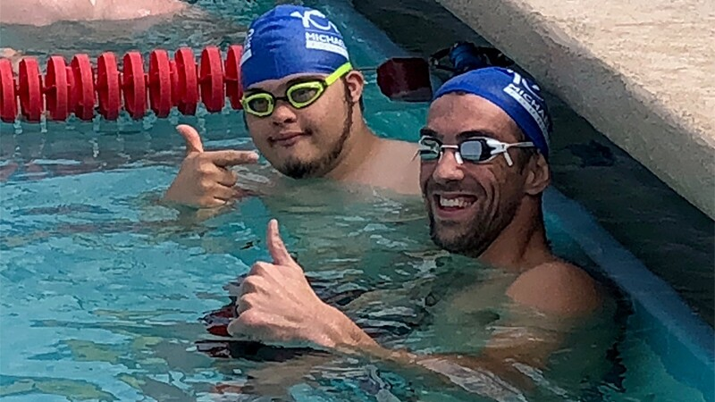 Micahel Pehlps in the pool with another athlete, but are giving a thumbs up