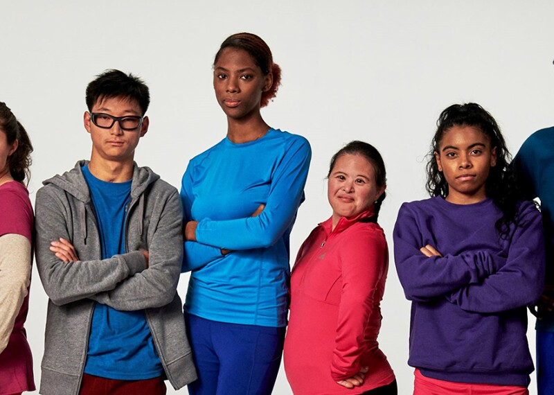 Group of seven young adults standing side by side for a group photo.
