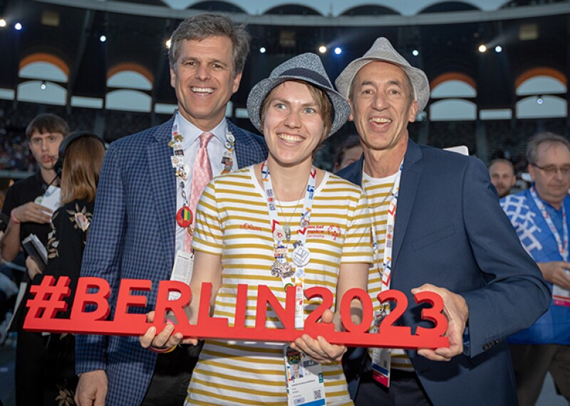 Three people in a stadium standing together in a group holding a sign that read: #berlin2023