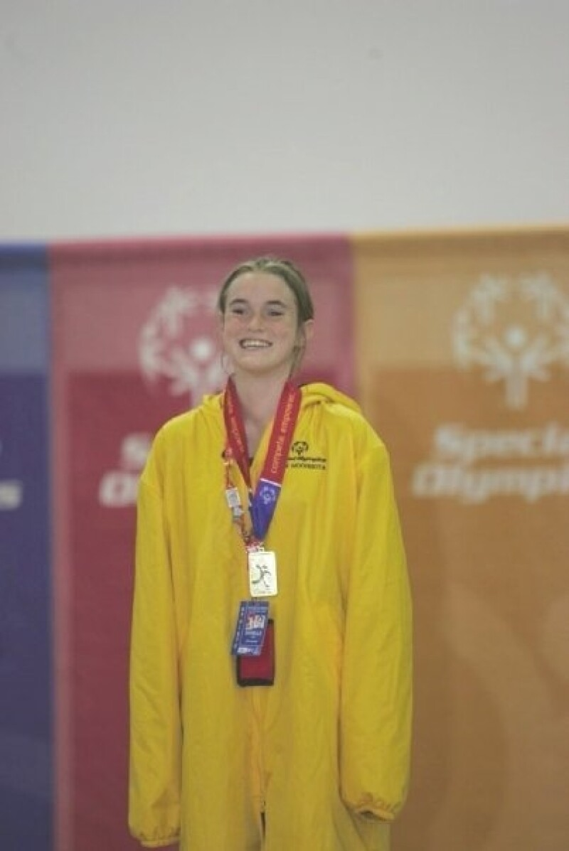 A Special Olympics athlete stands on the awards podium and smiles at the camera. She's wearing a medal.