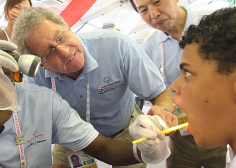A volunteer giving an athlete and oral exam while Dr. Perlman looks on.