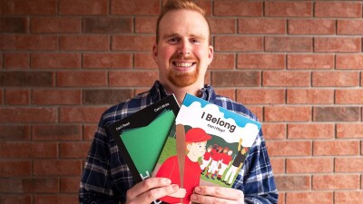 A Special Olympics athlete holds the two books he's written.
