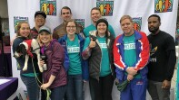 Special Olympics employees and friends (a group of 9) in front of a Best Buddies back drop.