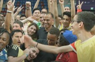 Cafu is smiling and wearing a black polo, surrounded by athletes and representatives; all are cheering.