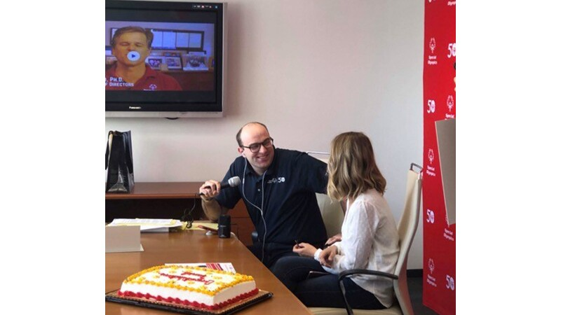 Dan talking with a host while he receives the news of becoming an International Global Ambassador. There is a congratulations cake on the desk.