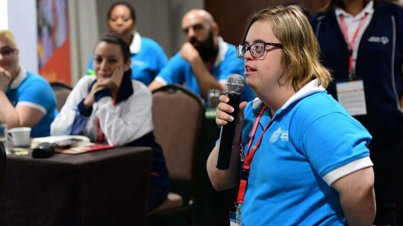 A female athlete leader holds a microphone as she talks at an event. People in the background listen to her.