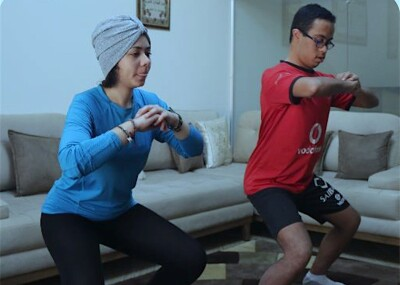 Heidi and Mohamed at home working out doing squats.