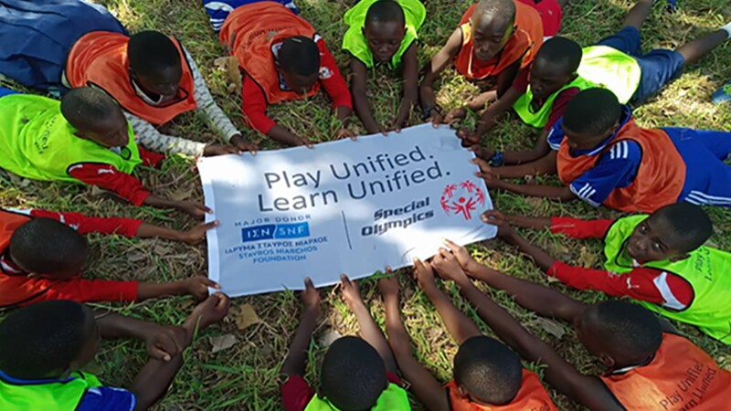 Special Olympics Tanzania youth lay in the grass in a circle in their football jerseys, holding a banner in the middle of them with the Play Unified: Learn Unified and Stavros Niarchos Foundation logo on it.