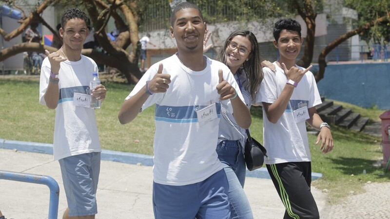 Four youth wave and give thumbs up to the camera mid-stride, at an outdoor campus. They are wearing matching Special Olympics shirts.