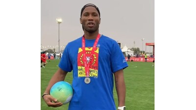 Man standing on the soccer pitch with a ball in his hand and a gold medal around his neck talking to the camera.