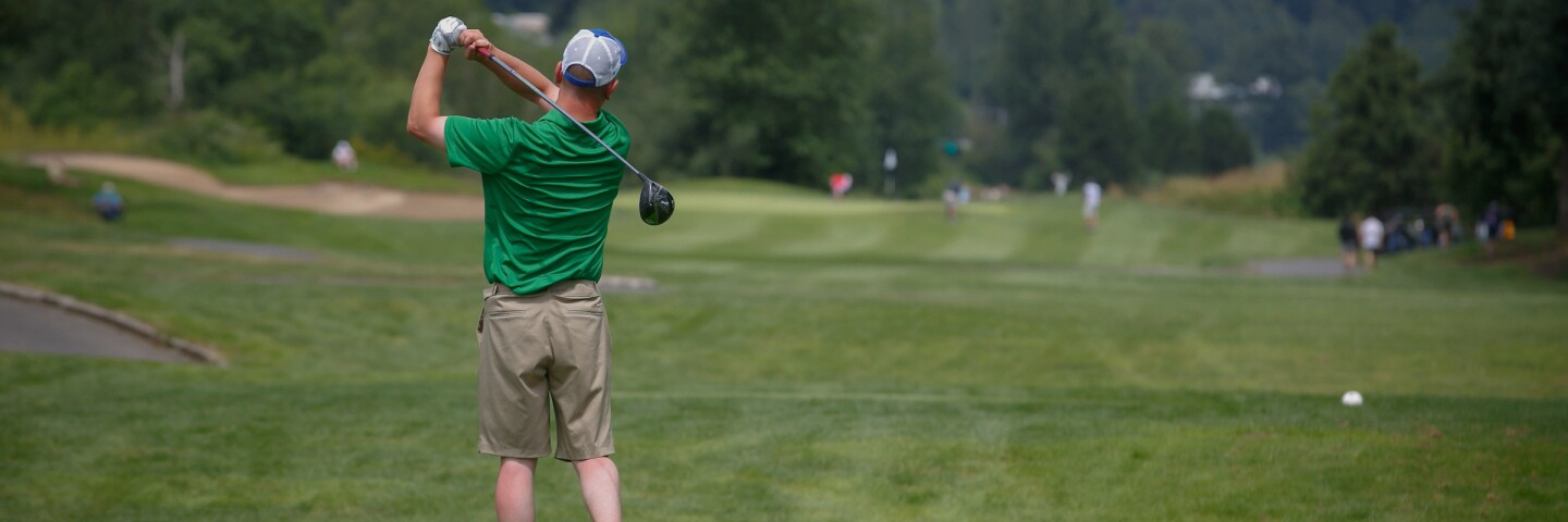 A male golfer just after striking the ball.