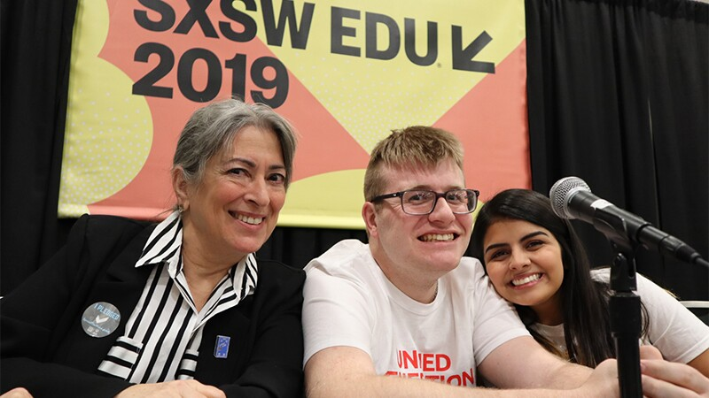 Three people, Andrea CahnMitch Bonar and Ivalis Guajardo, sitting at a pannel table together posing for a group photo in front of an SXSW EDU 2019 sign.