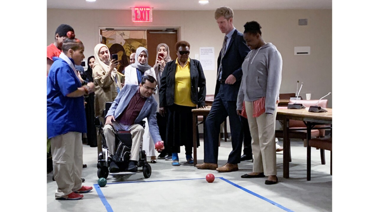 A group of young athletes and representatives play Bocce in a room at the UN.