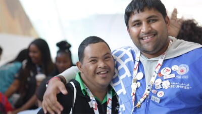 A volunteer with his arm around an athlete hugging him, both are smiling at the camera.