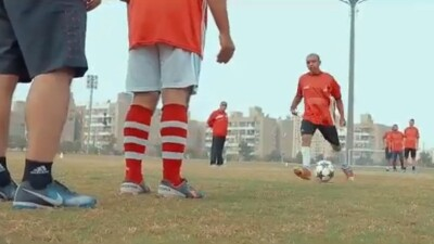 Football players are practicing dribbling the ball and working their way down the field toward the keeper to make a goal. On player has the ball, three are waiting, a ref is supervising; you can see the keeper and an assistance's legs in the foreground.