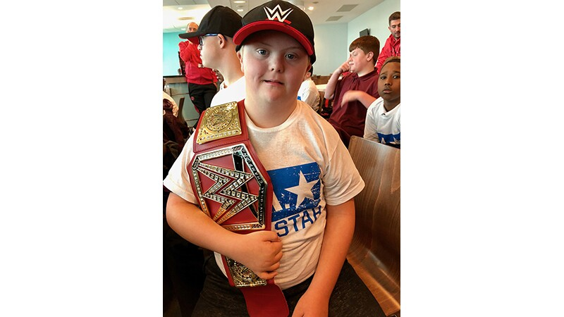 Brantwood Specialist School, Sheffield UK student has the title belt over his shoulder and is wearing a black and red WWE logo hat.