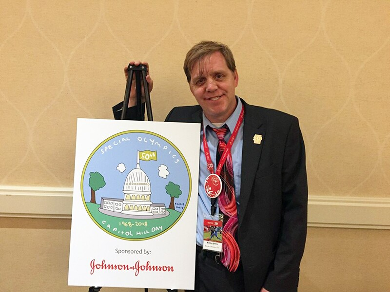 "Robert ""Bobby"" Jones standing next to a large version of his coloring book he made for the Special Olympics 50th Anniversary celebration. The coloring book was sponsored by Johnson and Johnson."