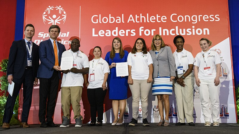 Special Olympics Chairman, Tim Shriver stands with leaders from the Global Athletes Congress standing on stage.