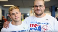 Two Special Olympics Team USA members standing side by side wearing Special Olympics USA t-shirts