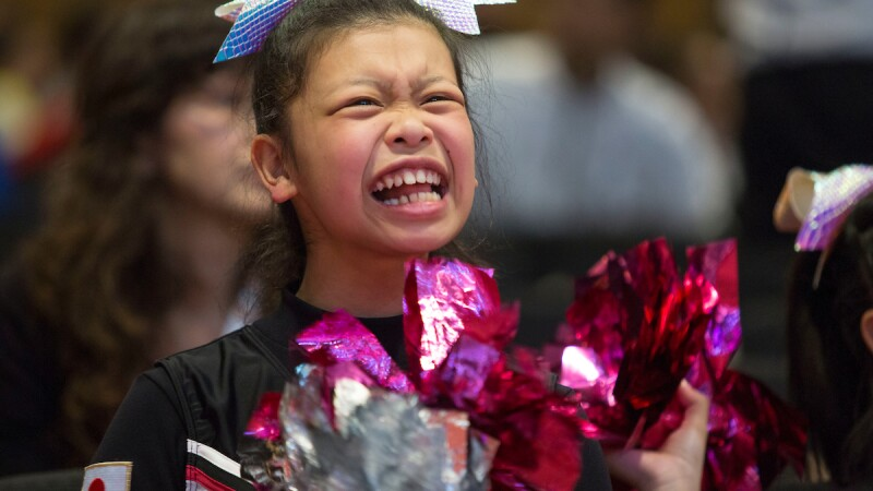Cheerleader for Japan cheering and ruffling her pompoms.