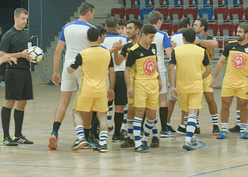 Special Athletes, Unified Athletes, and coaches shake hands and give one another high-fives on the court. One team is wearing yellow and black uniforms and the other is wearing blue and white uniforms.