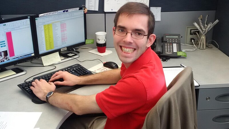 Tyler Leech sitting at his desk, turning around and smiling for a photo.