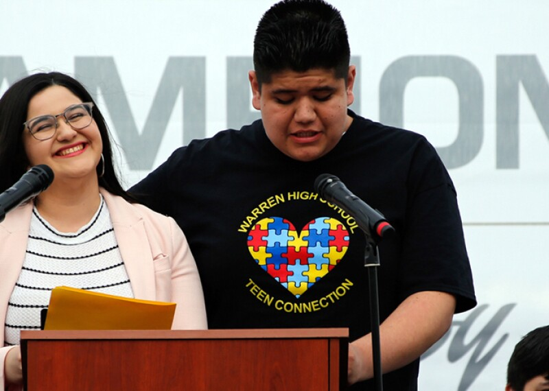 Young man and woman standing at a podium. The young woman is smiling and the young man is speaking.