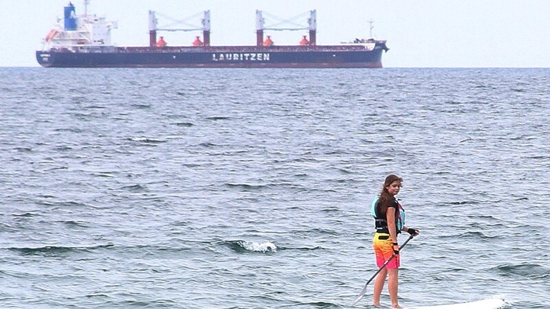 Special Olympics athlete rides paddleboard in ocean with large ship in background.