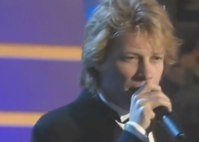 Jon Bon Jovi dressed up in a tuxedo singing on stage.