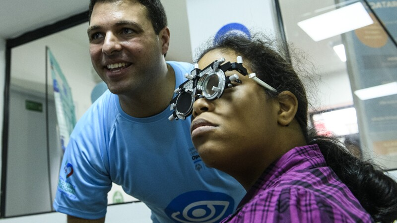 Athlete receiving an eye exam, volunteer standing next to her smiling and looking at results.
