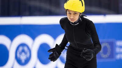 Speed Skater in all black with a yellow helmet preparing to skate.