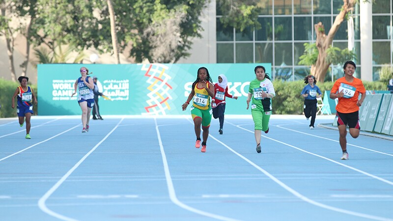 Seven athletes from all different countries on the track running.