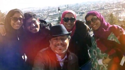 Ahmed and family in a photo taken outside overlooking a city.