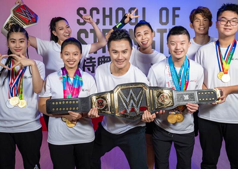 Athletes in a group holding a WWE championship belt.