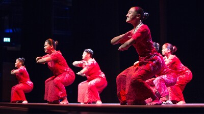 Six dancers on stage wearing red shirts and sarongs.