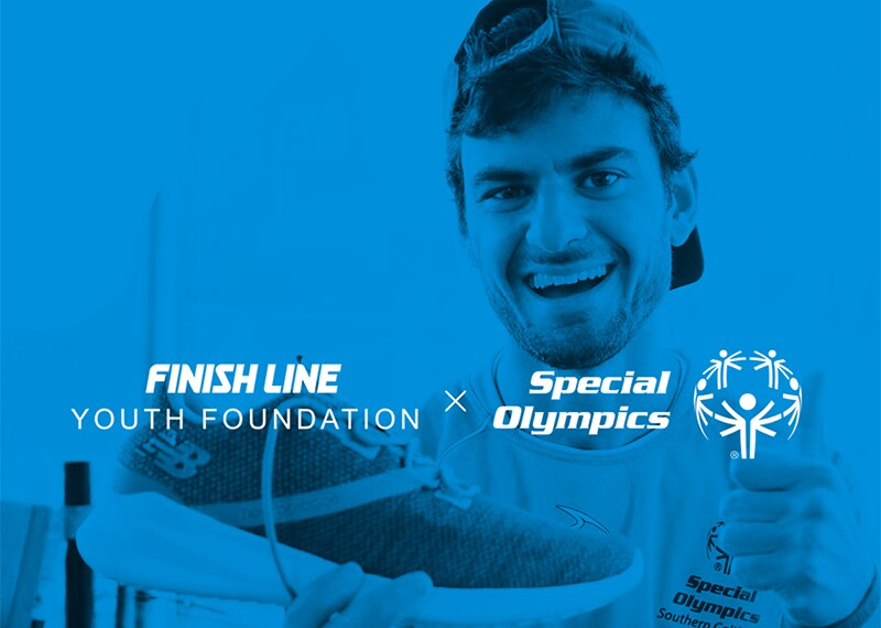 Athlete holding up a shoe with text across the front that reads: Finish Line Youth Foundation and Special Olympics