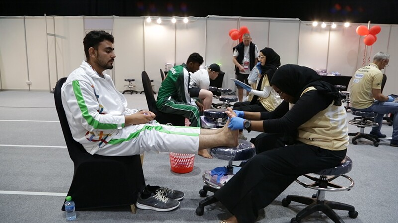 Athlete sitting in a chair receiving a foot examination by a health volunteer.