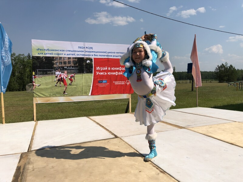 A child on a stage dancing in traditional costume in front of a Special Olympics and Stavros Niarchos Foundation poster.