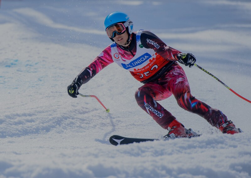 Female athlete skiing down hill.