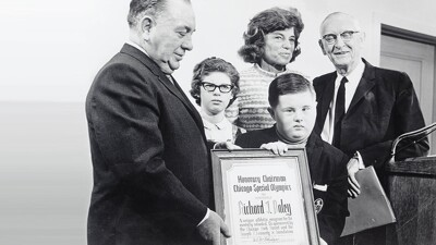 Black and white photo of Eunice Kennedy Shriver, Richard Daley, Melanie and Kevin O'Brien and representative. Richard Daley is presenting an Honorary Chairman Chicago Special Olympics document to Kevin.