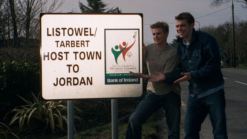 Two young man on the side of the road pointing to a sign that reads: Listowel/Tarbert Host Town to Jordan.