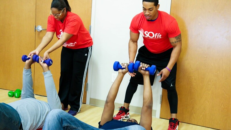 Two SO Fit coaches in red shirts and black athletic bottoms, standing above athletes that are laying on the floor that are performing chest presses with light weights.